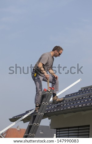 worker preparing the roof to install alternative energy photovoltaic solar panels.