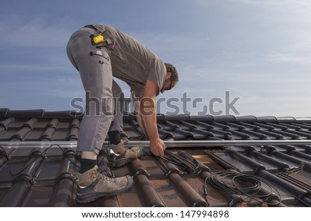 worker preparing the roof to install photovoltaic solar panels. - stock photo