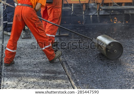 Worker pushing hand roller for mastic asphalt paving, making asphalt with coated chippings. Selective focus and shallow dof, some motion blur present. - stock photo