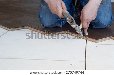 Worker puts oak parquet and hammered nails into it. - stock photo