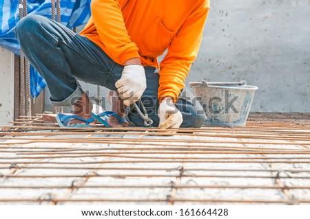 Worker, rebar gridwork across a floor for strength - stock photo