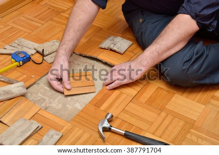 Worker repairing parquet in apartment damaged by moisture or water - stock photo