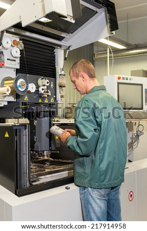 Worker- repairman operating industrial cnc machine in workshop. Metalworking and engineering industry, lathe , cnc and milling technology. - stock photo