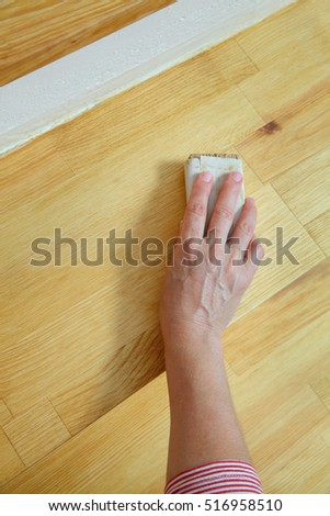 Worker sanding plank at stairs using sand paper, closeup of hand