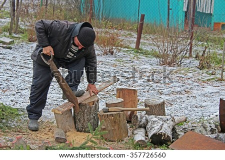 Worker sawing boards in a country house