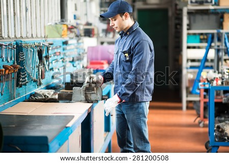 Worker securing a metal plate in a vise - stock photo