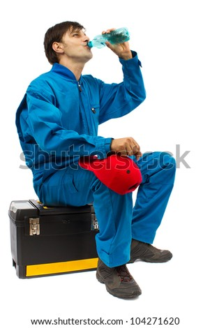 worker sitting on the toolbox drinking water isolated on a white background - stock photo