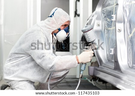worker spraying grey paint on a car in special painting booth