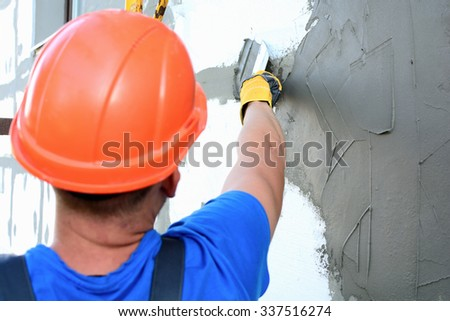 Worker spreading mortar over styrofoam insulation
