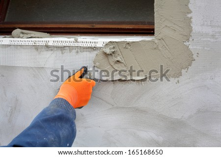Worker spreading  mortar over styrofoam insulation with trowel - stock photo