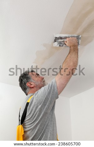Worker spreading  plaster to ceiling with trowel, repairing works