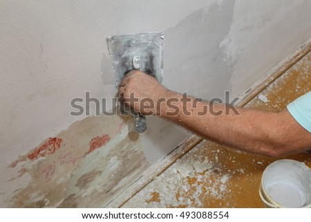 Worker spreading  plaster to damaged wall, repairing works