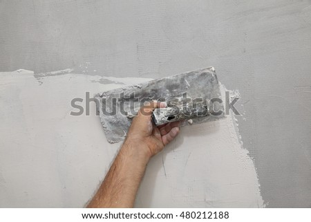 Worker spreading  plaster to wall, repairing works