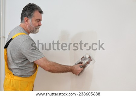 Worker spreading  plaster to wall with trowel, repairing works - stock photo