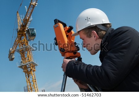 worker surveyor measuring distances, elevations and directions on construction site by theodolite level transit equipment
