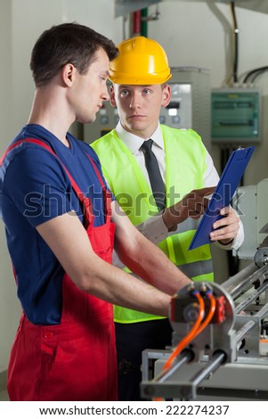 Worker talking with boss in a factory