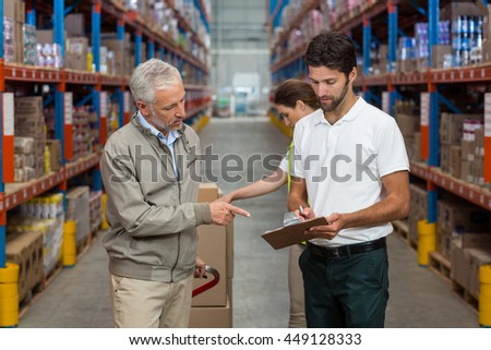 Worker team is looking a clipboard in a warehouse