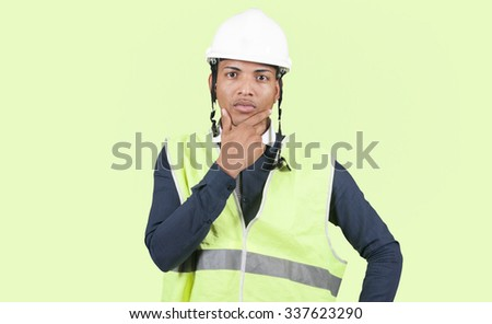 Worker thinking on green background - stock photo