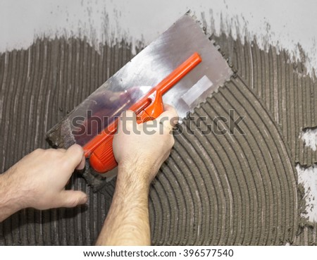 Worker tiler put cement on the wall - stock photo