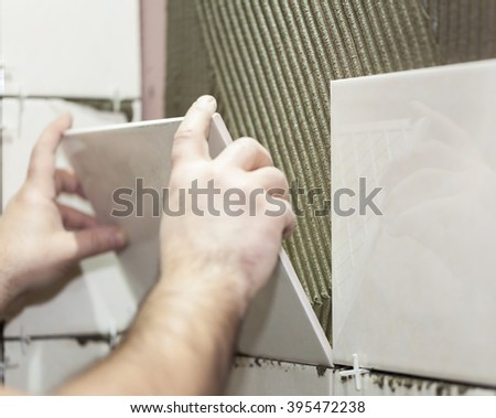 Worker tiler puts ceramic tiles on a wall - stock photo
