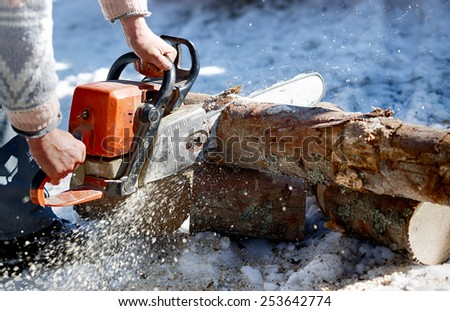 Worker trimming wood with chainsaw during winter - stock photo