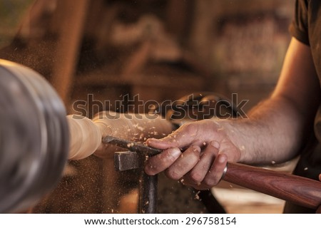 worker turning wood on a lathe - stock photo