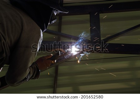 worker us electric welding connecting construction metal
