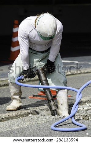 Worker use Jackhammer drilling cement concrete road, road repairing work