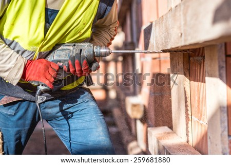 Worker using a drilling power tool on construction site and creating holes in bricks  - stock photo