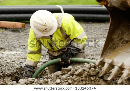 Worker using a small tracked excavator to dig a hole to fix a water leak at a large commercial housing development in Oregon - stock photo