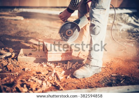 worker using an angle grinder on construction site for cutting bricks, debris. Tools and bricks on new building site - stock photo