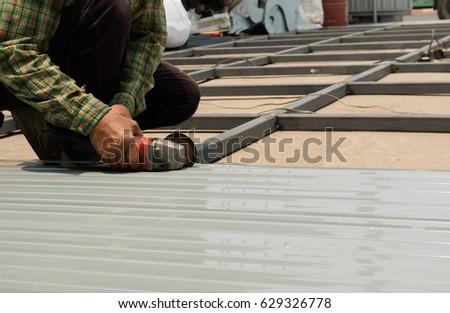 Worker Using Grinder Machine To Cut Metal Roof.Cut Steel Plate.