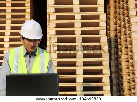 worker using laptop with stacking pallet background - stock photo