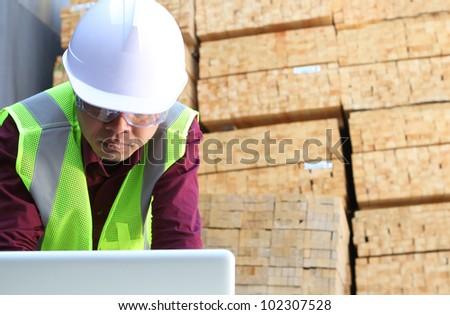 worker using laptop with stacking wood background - stock photo