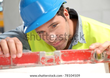 Worker using level on building site - stock photo