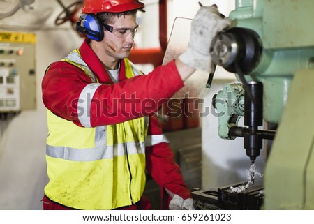 Worker using machinery on oil rig