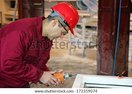 Worker Using Power Tool in Workshop. Worker at Workshop. PVC windows and doors manufacturing. - stock photo