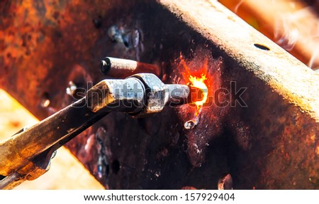 worker using torch cutter to cut through metal - stock photo