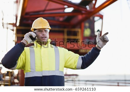 Worker using walkie talkie on oil rig