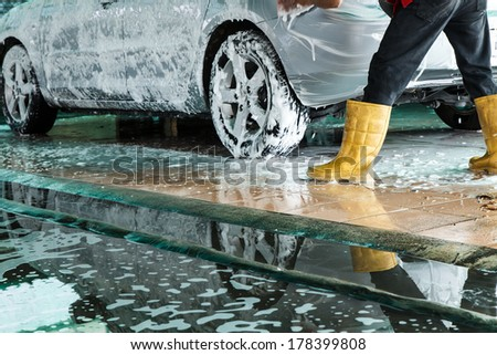 Worker washing car in the carwash - stock photo