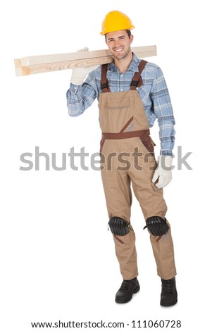 Worker wearing hard hat and carrying timber. Isolated on white