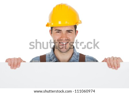 Worker wearing hard hat and holding empty banner. Isolated on white - stock photo