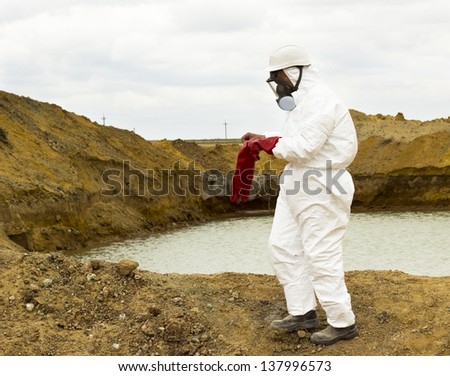 worker wears protective clothing and mask costs about poisoned lake on the industrial site