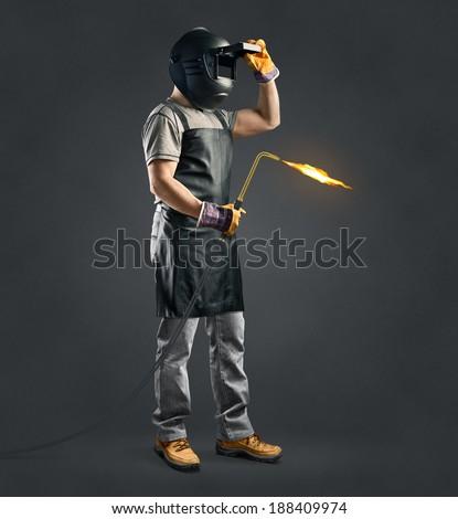 worker welder with gas welding machine on gray background  - stock photo