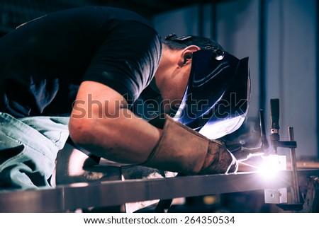 Worker welding aluminum using tig welder - stock photo