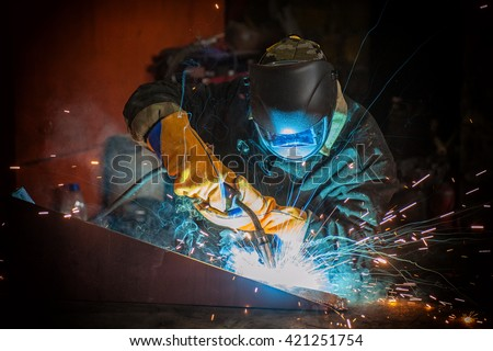worker welding metal with sparks at factory - stock photo