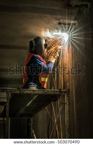 worker welding metal with sparks in construction site