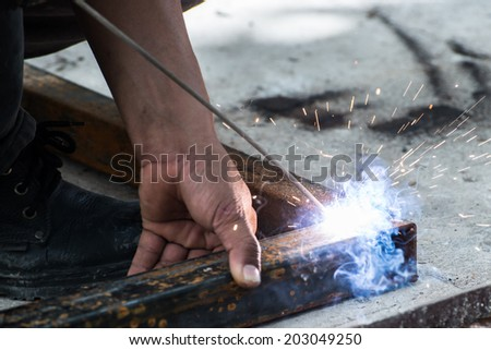 Worker welding steel with sparks lighting - stock photo