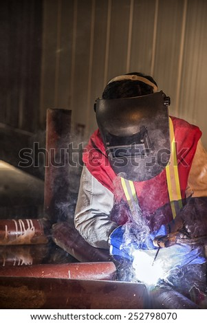 Worker welding the steel part by manual at Construction Site - stock photo