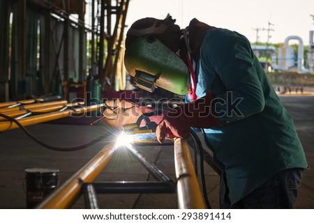 Worker welding the steel structure - stock photo